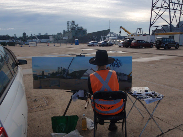 Artist Jane Bennett at her easel painting plein air canvas of ex HMAS Adelaide at Glebe Island Wharf by marine and industrial heritage artist Jane Bennett
