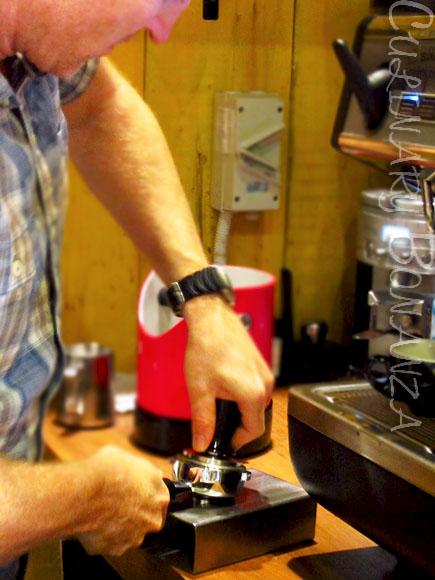 Saxon Wright tamping ground coffee