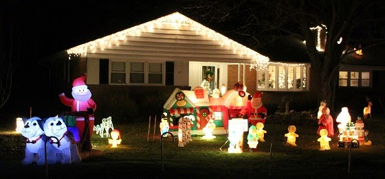 House front yard with many Inflatable outdoor Christmas decorations