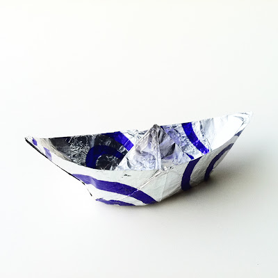 A miniature origami boat made out of silver and blue biscuit wrapper.