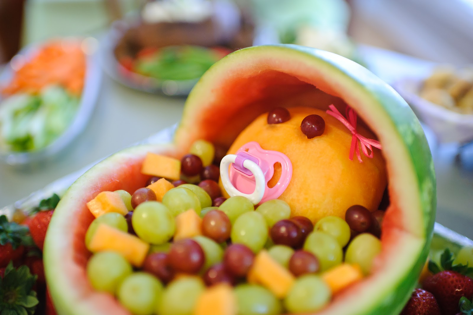 place fruit head in watermelon bassinet and surround with fruit
