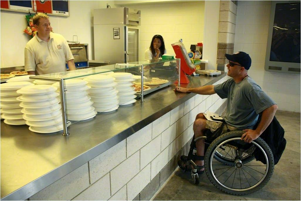 this picture shows a manual wheelchair user at an inappropriately designed counter trying to get service from a blonde headed men and a brunette headed women
