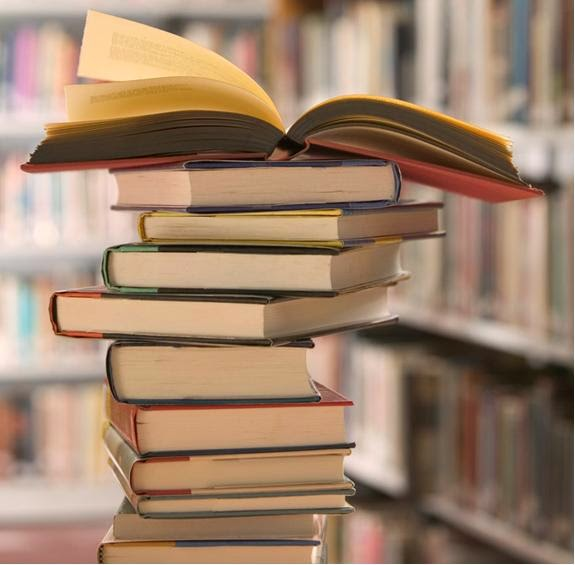 A tall stack of library books with on open book on top.