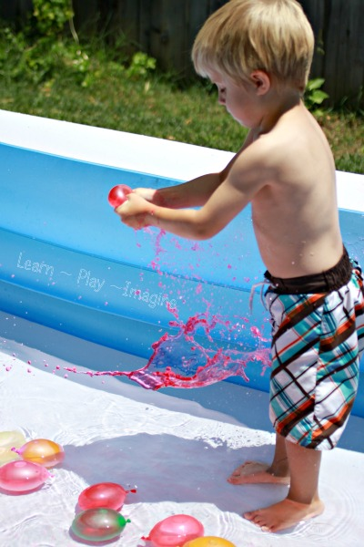 Popping balloons filled with colored water for summer fun to beat the heat