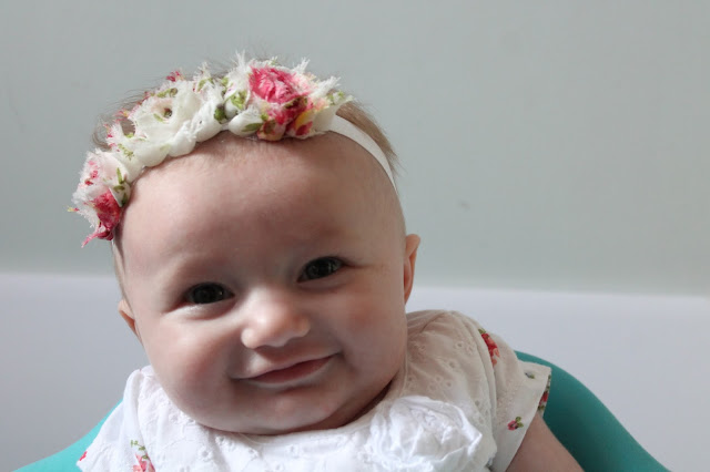 Portrait photo of baby girl smiling wearing shabby chic rose headband