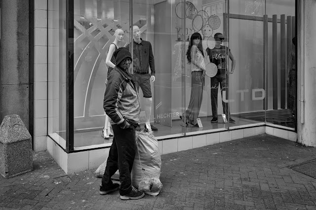 A man stands in front of a storefront window with mannequins in it.