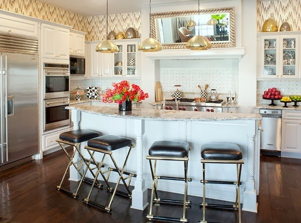 Kourtney Kardashian's kitchen with gold pendant lights, stainless appliances, silver bar stools and a white island
