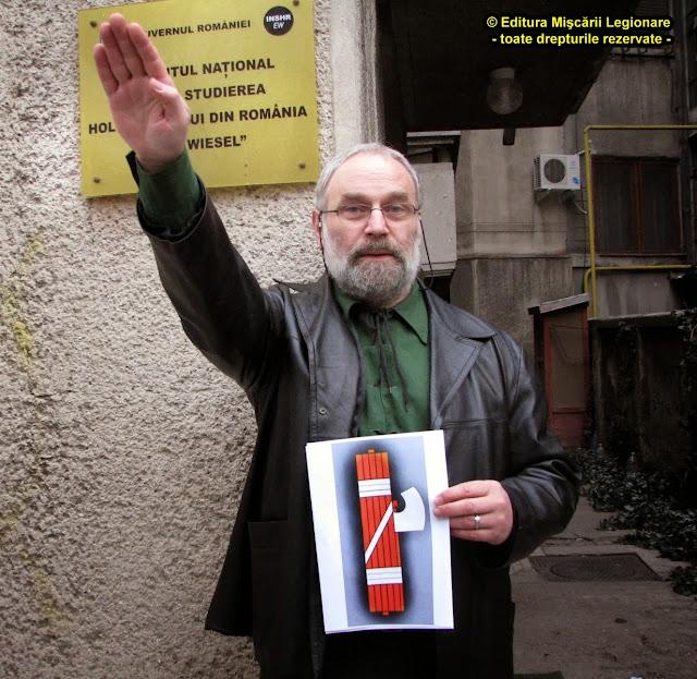 Serban Suru salutand cu un simbol al M.A.I. in mana.