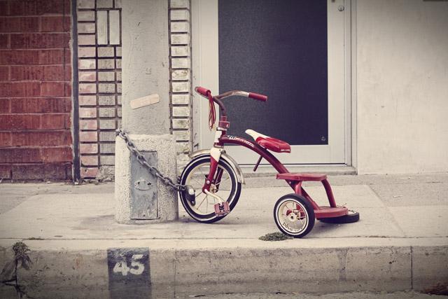 Triciclo de niño sujetado con una cadena