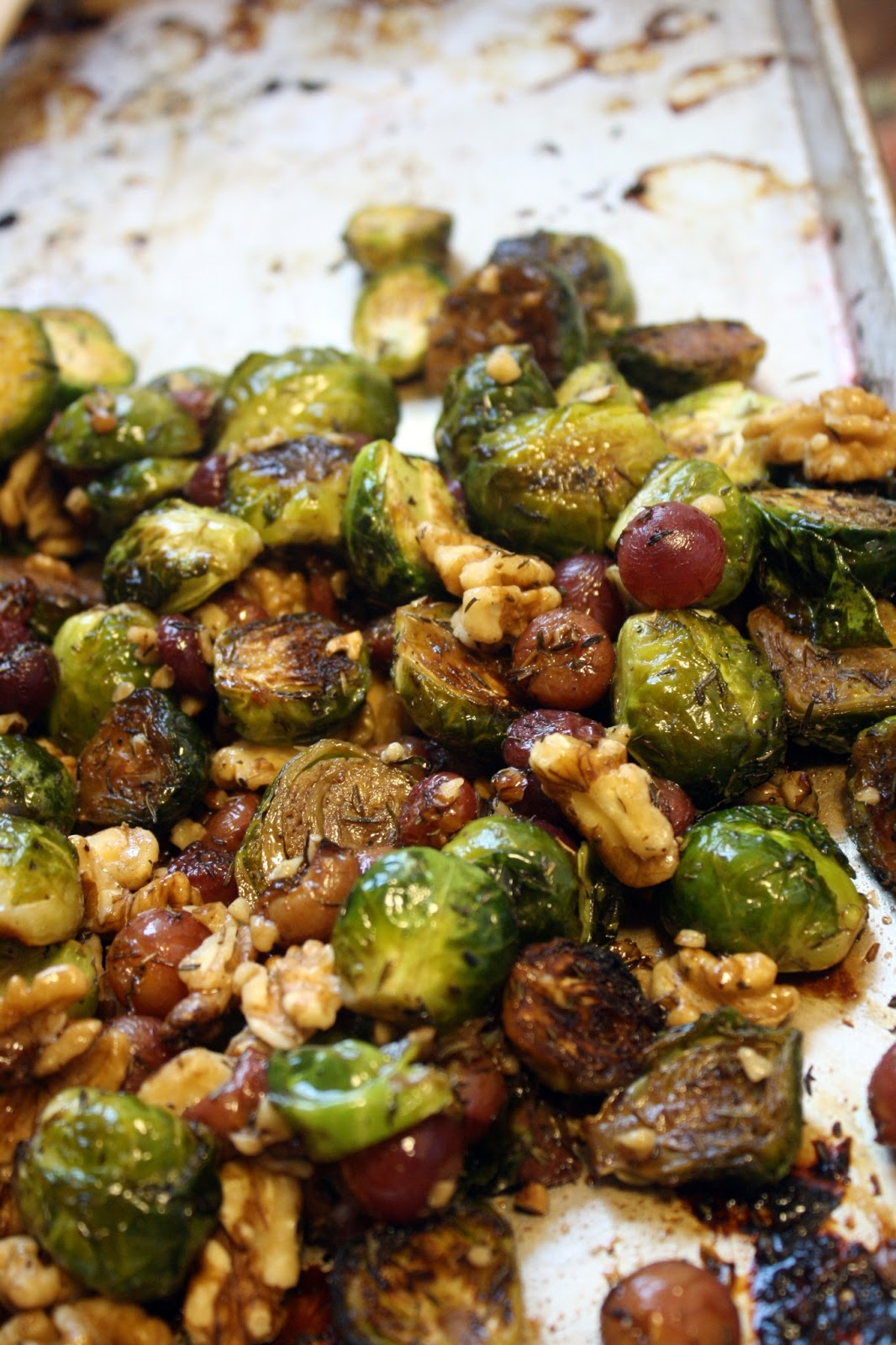 and pepper tossed brussels sprouts and grapes on a baking sheet ...