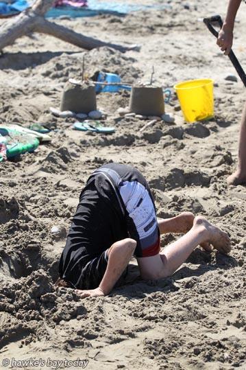 Kiwi Ostrich - Boy digs a hole in Waimarama Beach photograph