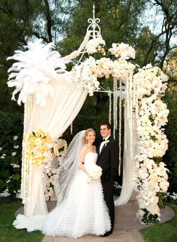 effect of mixing flowers fabric and feathers in this wedding gazebo