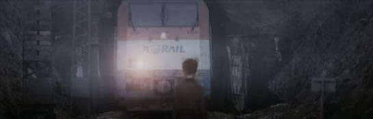 A small boy stands before an oncoming train.