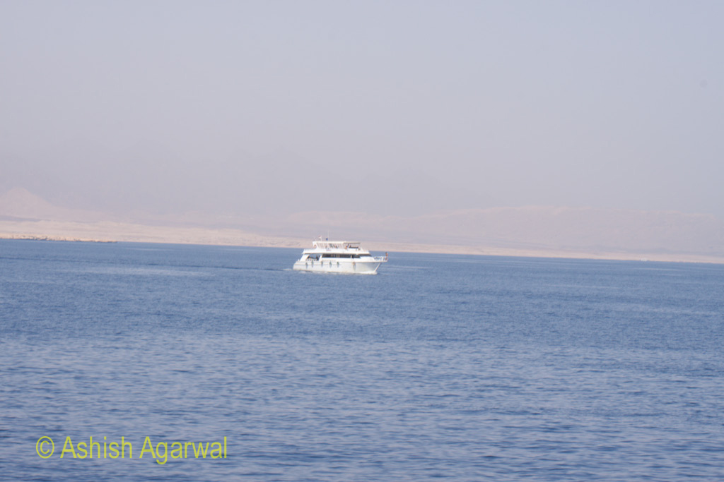 A tourist ship in the waters of the Red Sea with the coastline in the background