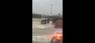 It shows a man getting washed away in a dangerously flooded unidentified street. But passersby rush to his aid, form a human chain and pull him out. The man is saved from a definite watery grave.   The quality if video is grainy - but the human spirit shines through it .