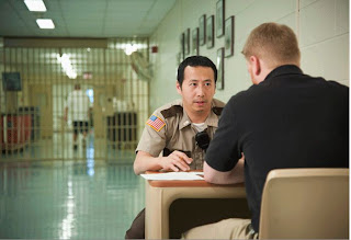 A correction officer interviews an inmate outside prison doors.
