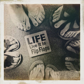 Five people in a circle showing toes, toe rings, flip flops and sign Life Live It In Flip Flops