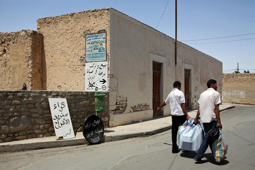 Dois homens transportando um volume, caminhando pelo meio da rua.