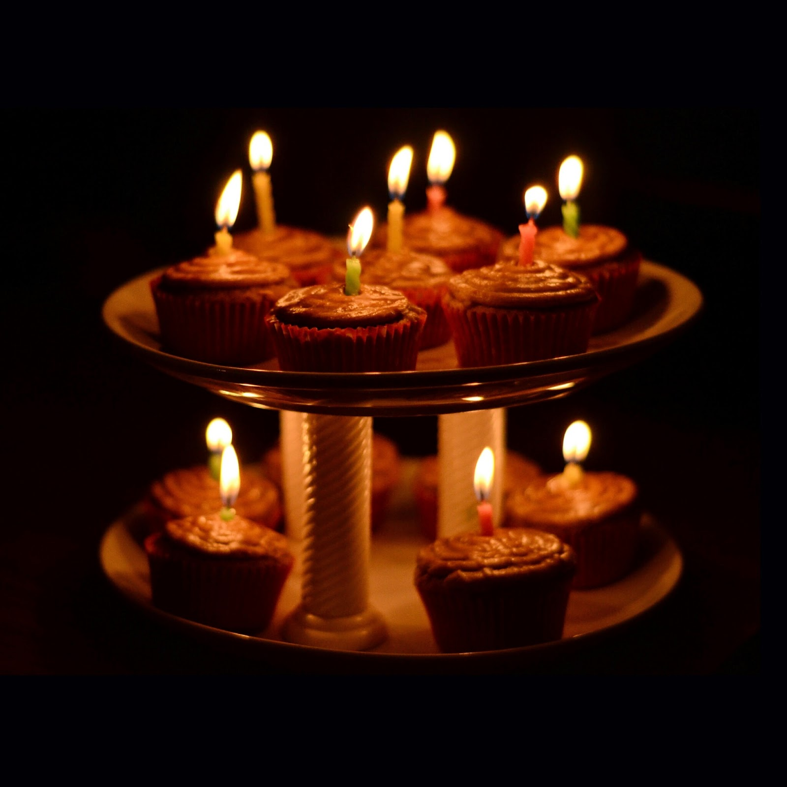 Celebrating a birthday by baking a tower of salted caramel cupcakes decorated with lit candles at midnight