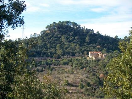 Vista del Mas de Sant Jaume i al seu darrere el Turó del Castell, des del camí de la banda assolellada del Turó de Montgoi