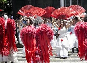 Descrição: Foto de mulheres com trajes folclóricos. Elas usam vestidos brancos longos, duas rosas vermelhas como enfeite, uma no ombro e outra na saia. Erguem um grande leque vermelho sobre a cabeça. De costas, pessoas com asas vermelhas.  Fim da descrição.