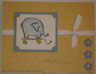 Yellow baby card with stamped image of an elephant pull toy.