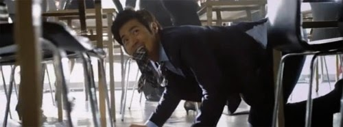 Detective Yang Choon Dong, tie in mouth, crawls through rows of desks.