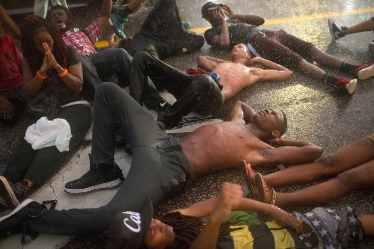 70 Of The Most Touching Photos Taken In 2015 - Protesters block a highway and play dead to mark the one-year anniversary of the shooting of Michael Brown.