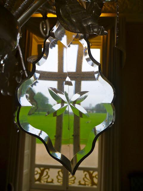 Blick durch ein Kronleuchterlement auf ein Fenster mit dahinterliegender grüner Wiese