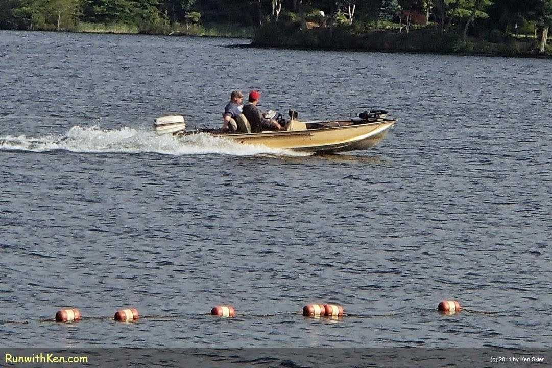 Photo of a small powerboat, and discussion of how to stay safe while open water swimming.