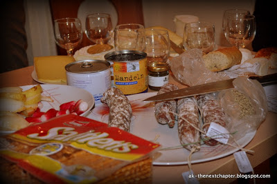 Close-up of a table with wine glasses, and various snacks - sausages and salami in the middle