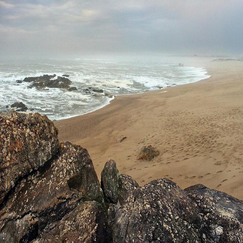 Um conjunto da grandes rochas em primeiro plano, a seguir a praia, o mar e o horizonte muito nubloso