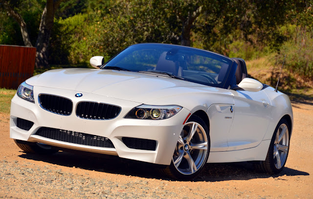Front 3/4 view of white 2012 BMW Z4 parked with top down in country setting