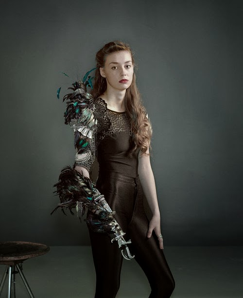 Woman with prosthetic right arm, decorated with multicolored feathers