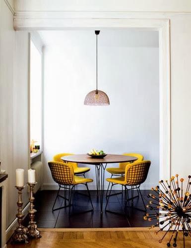 Czarne druciane krzesła i żółte siedziska w eleganckiej aranżacji