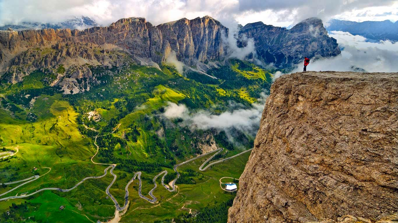 Trekker on the Sella Group mountain chain, looking down on the road from Badia Valley to Gardena Pass, Dolomites, South Tyrol, Italy (© SIME/eStock Photo) 268