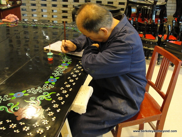 man painting design on laqueur table gift shop at factory reproducing Terracotta Warriors souvenirs in Xi'an, China
