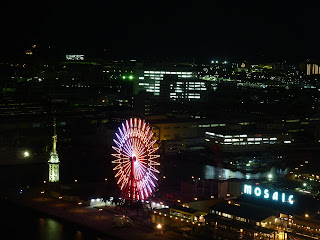 Ferris wheel lit up with pink lights in Harbour land as seen from the top of the Kobe Port tower at night
