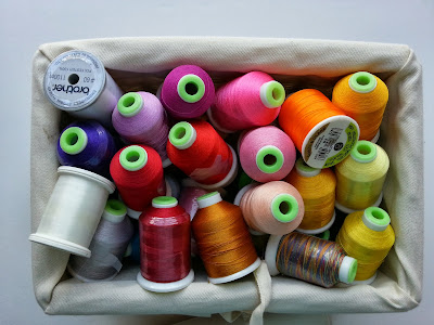 spools of thread in all the colors of the rainbow piled in a basket
