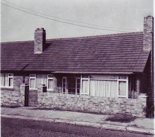 A greyscale photo of a small semi detached bungalow.  The front door is glazed in squares, with matching panels of squares of glass on either side.  There are two windows, one a large square bay.  The small front garden is separated from the pavement by a low wall and gate.  The bungalow looks a little low set, there may be steps or a ramp down from the gate to the door.