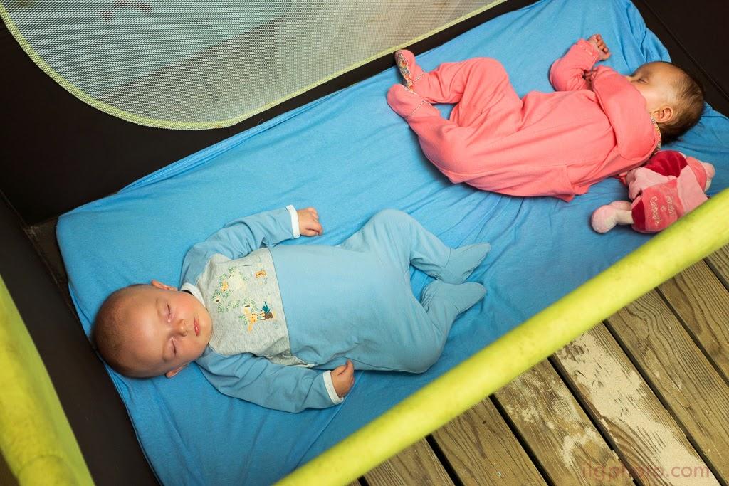 Deux bébés dorment dans un lit portable