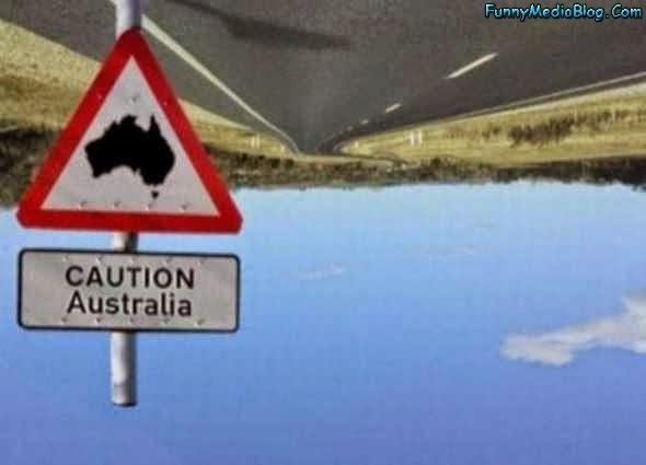 Upside down photo of a sky and road with a caution sign for Australia