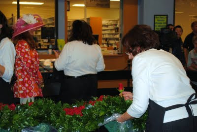 two women putting red roses on the garland at kroger the night before derby