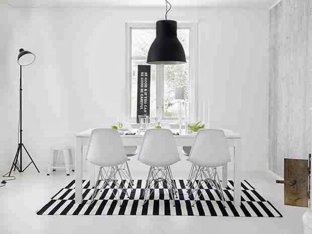 Białe wnętrze, dywan w pasy biało-czarne, białe krzesła, czarna stojąca lampa, industrialna wisząca lampa