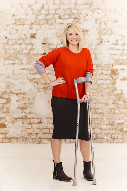 red cashmere jumper, model with crutches,