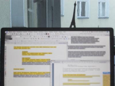 Ein unscharf gestellter Monitor vor einem Fenster, auf dem drei unterschiedliche Texte abgebildet sind. Etliche Textstellen sind farblich markiert.