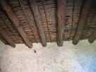Detall del sostre fet de bigues de fusta i encanyissat del cobert de les tines del mas Rubió