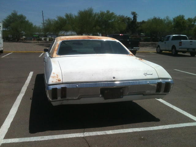 Rear view of 1970 Chevrolet Bel Air with rusty roof and rear fender parked in parking lot