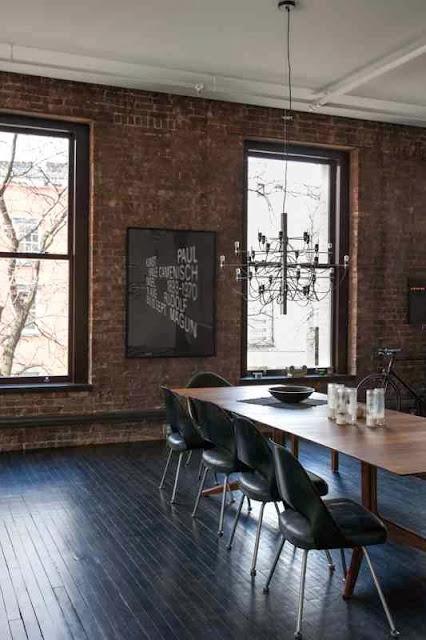 Loft i czarna podłoga z desek, ściany z cegły w lofcie, czarne krzesła, czarna grafika na ścianie z cegły