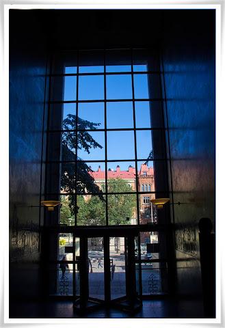 Fotat inifrån Stadsbiblioteket mot blå himmel, som speglar sig i väggarna